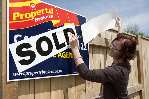 Putting up sold sign
